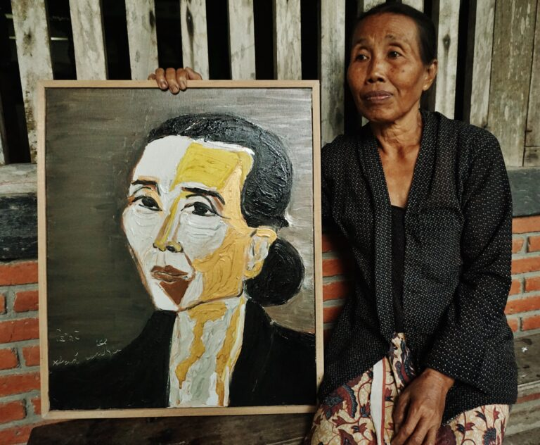 An olive skinned woman sits behind a painting on the floor, against the backdrop of a wooden door. The painting titled 'Paini' depicts a portrait of the woman in a tied bun and wearing a black shirt.