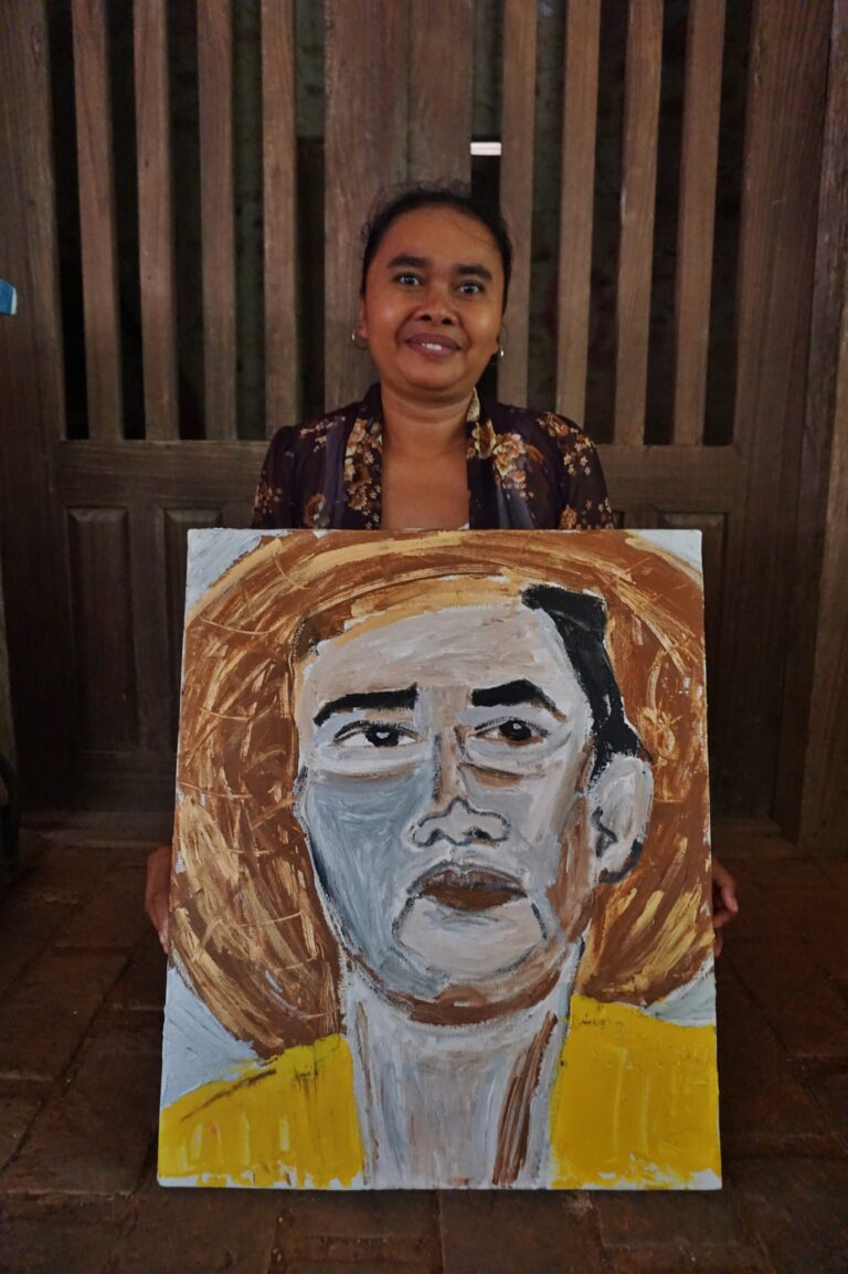 An olive skinned woman sits behind a painting on the floor, against the backdrop of a wooden door. The painting titled 'Ambarwati' depicts a portrait of the woman wearing a yellow shirt and a conical hat.