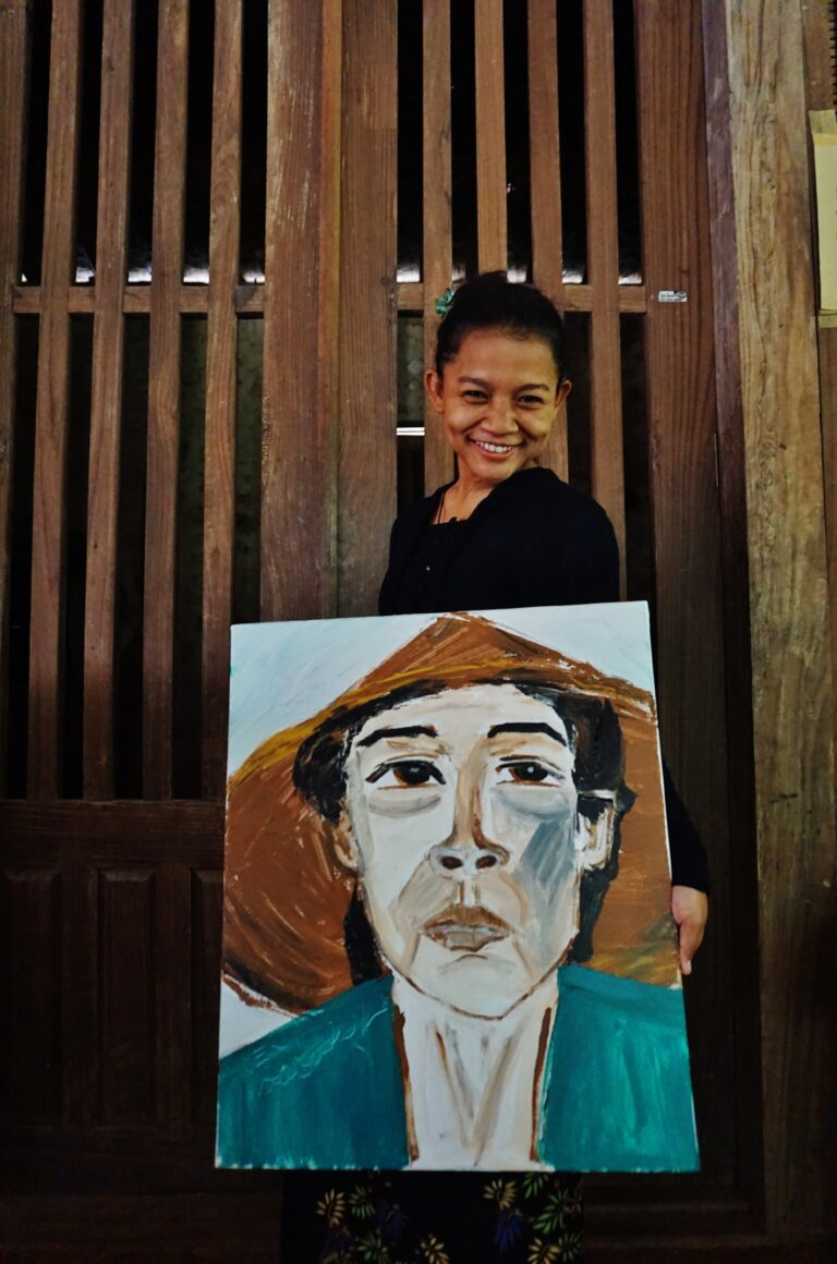 An olive skinned woman stands behind a painting on the floor, against the backdrop of a wooden door. She is smiling. The painting titled 'DENI' depicts a portrait of the woman wearing a teal coloured shirt and a conical hat.