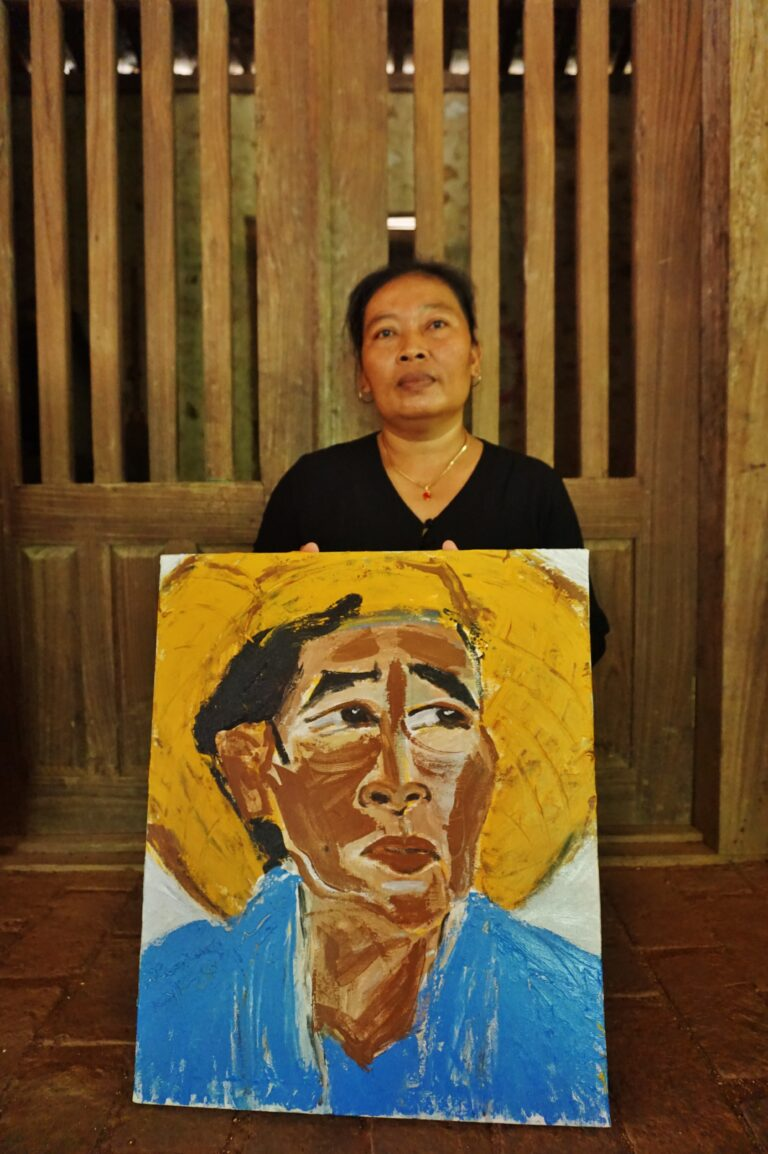 An olive skinned woman wearing a black shirt sits behind a painting on the floor, against the backdrop of a wooden door. The painting titled 'Karsupi' depicts a portrait of the woman wearing a blue shirt and a conical hat.