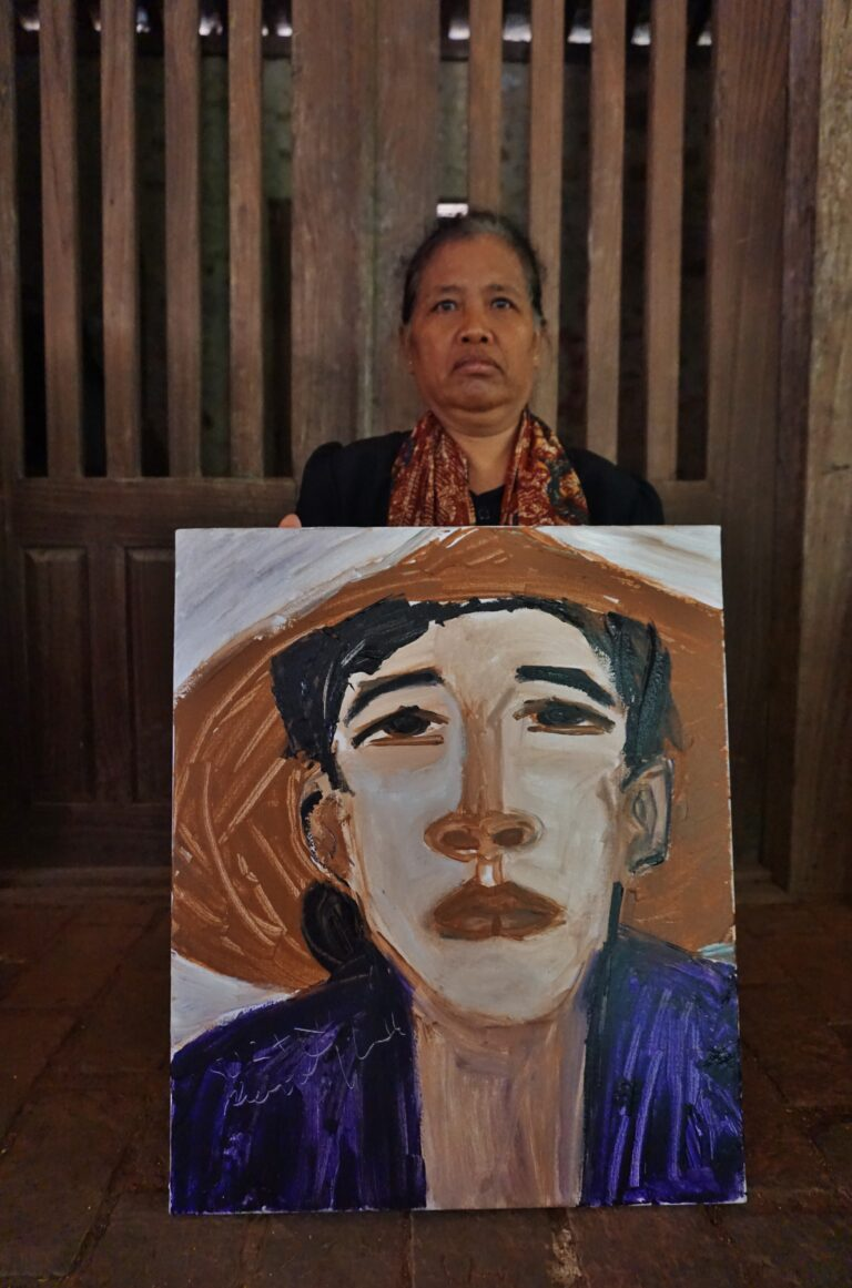 A tanned skin woman standing behind an oil portrait of herself. She is wearing a conical hat and a purple shirt in the painting.